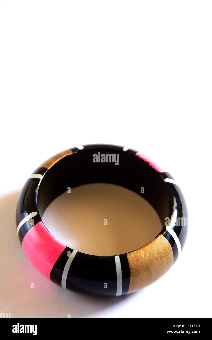 Colourful wooden bangle on white background - Stock Image