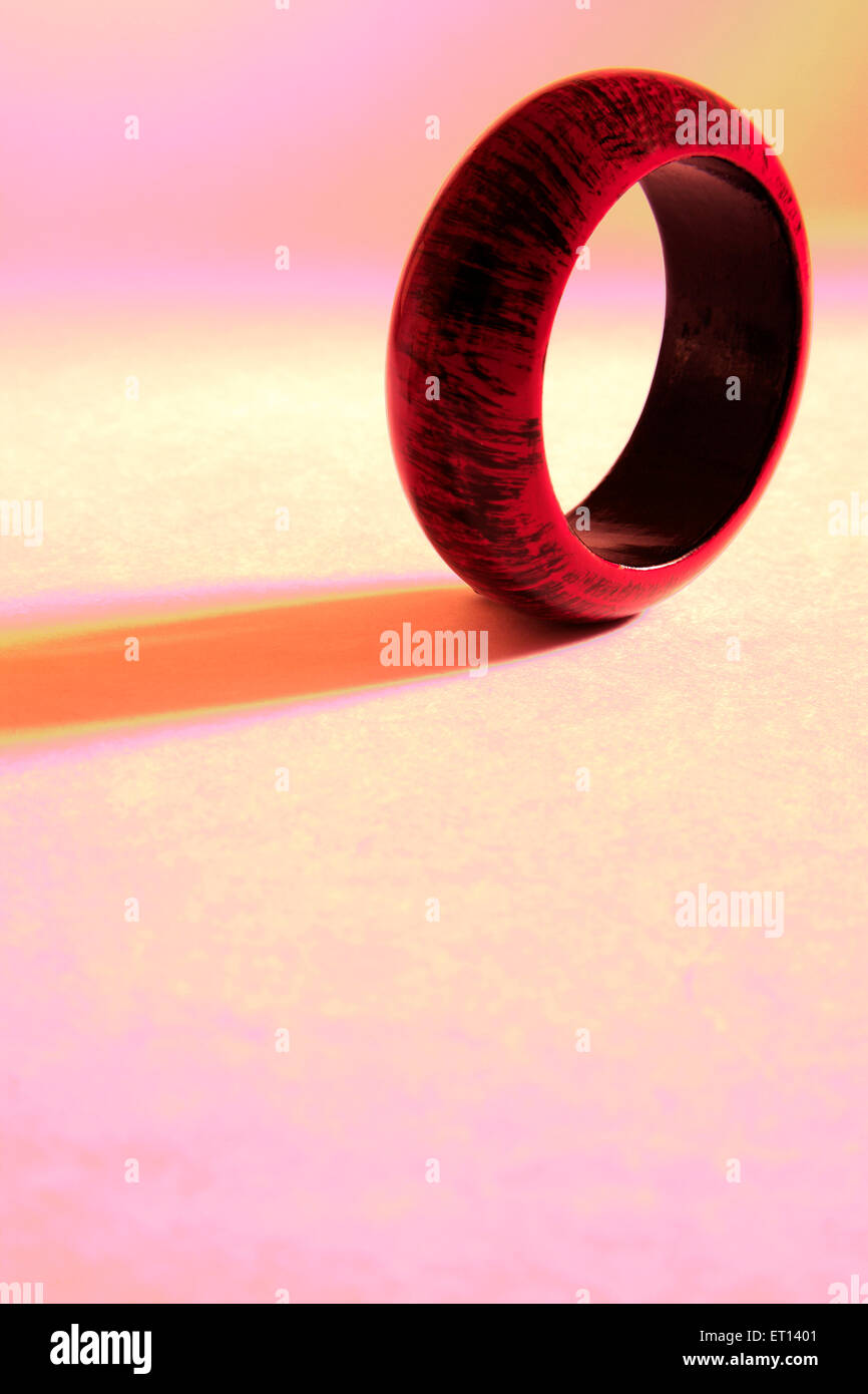 Maroon and black colours on wooden bangle on white background - Stock Image
