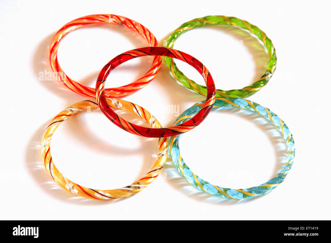 Colourful glass bangles on white background - Stock Image