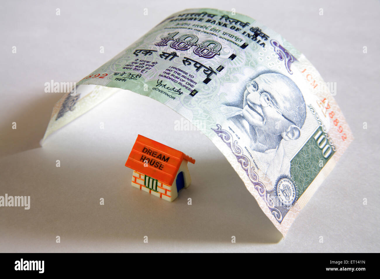 Plastic home model below notes of hundred rupees on white background - Stock Image