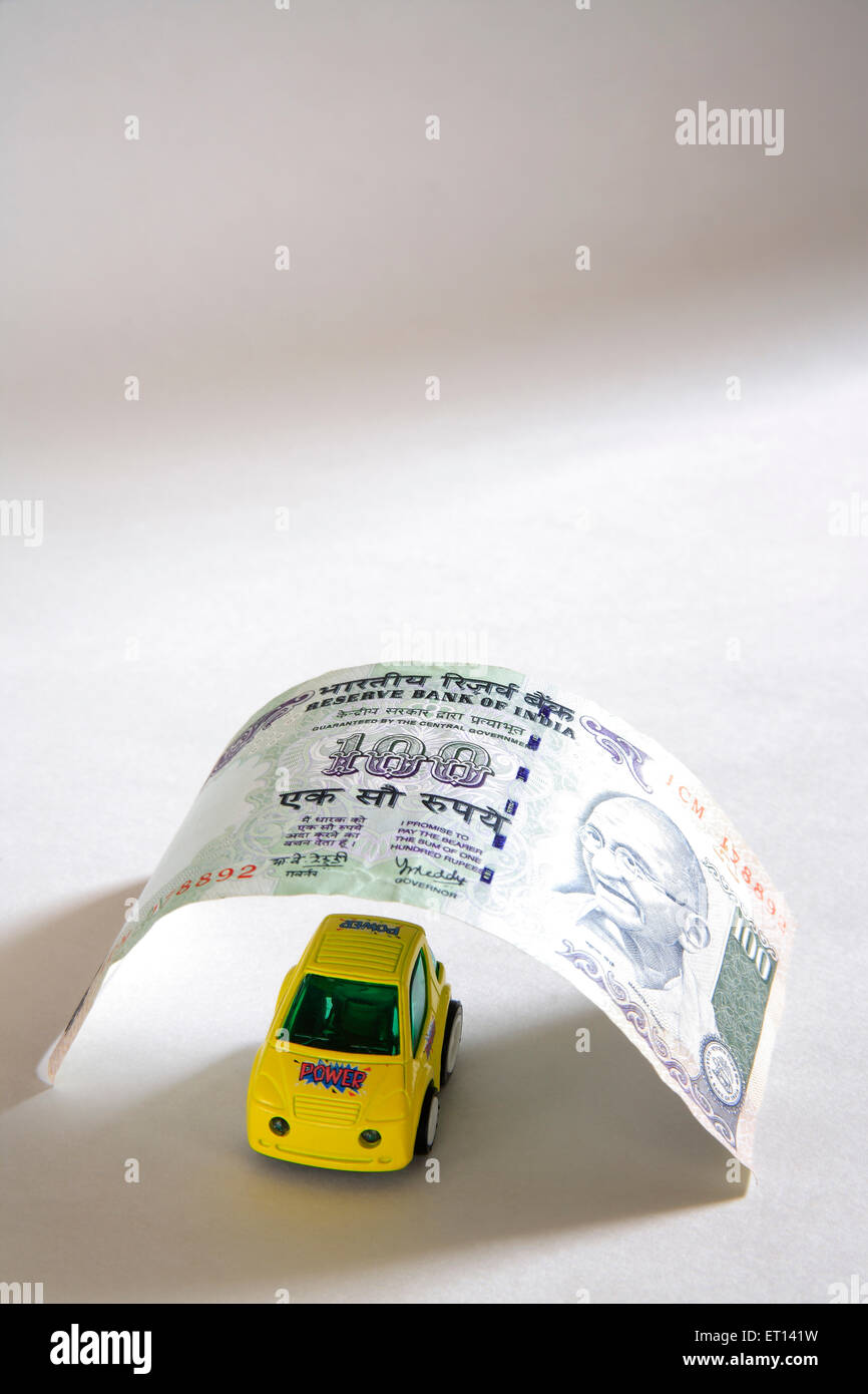 Plastic yellow car model below notes of hundred rupees on white background - Stock Image