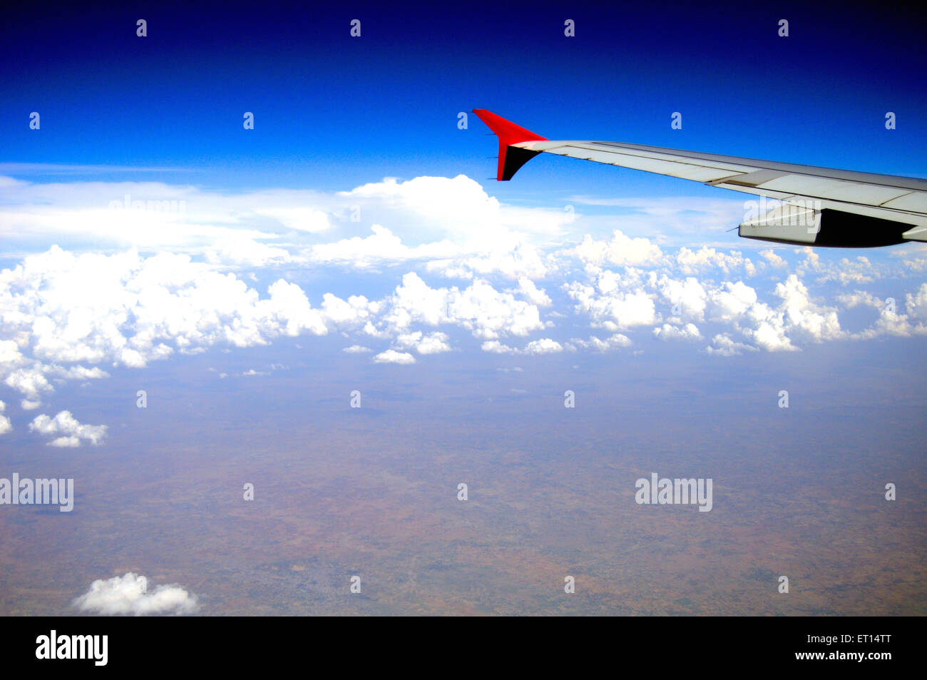 Aerial view of aeroplane wing in blue sky - Stock Image