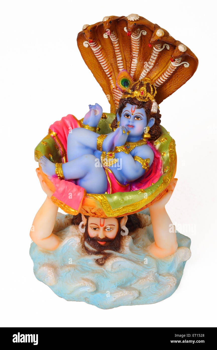 Clay statue of bal krishna with father vasudev and snake - Stock Image