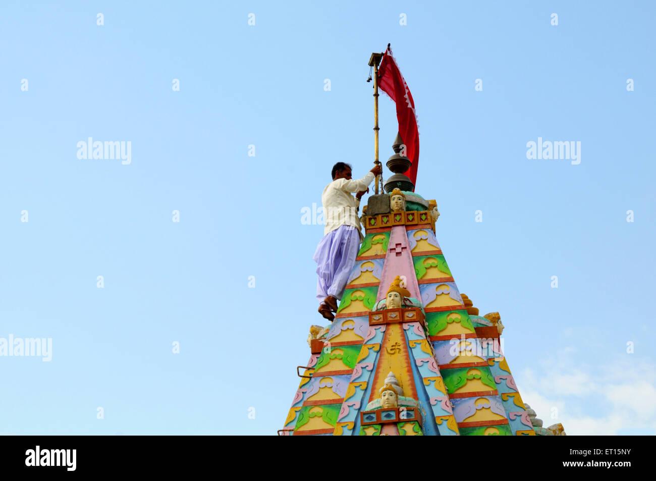 Tying flag mast to pole on top of temple at Mindiyada near Anjaar ; Kutch ; Gujarat ; India - Stock Image