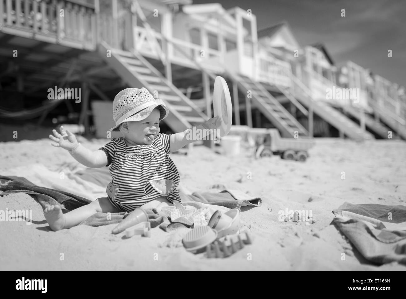 baby girl sitting in the sand on the beach playing and laughing - Stock Image