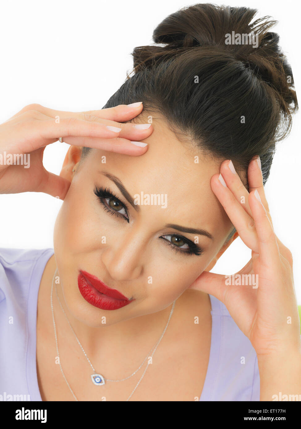 Beautiful Young Hispanic Woman Suffering With A headache and Feeling Unwell Shot Against A White Background - Stock Image