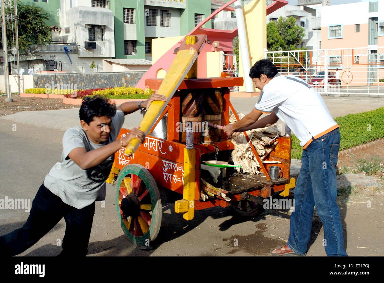 Man extracting sugar cane juice from manual sugarcane juice making machine , Nasik , Maharashtra , India MR#364 - Stock Image