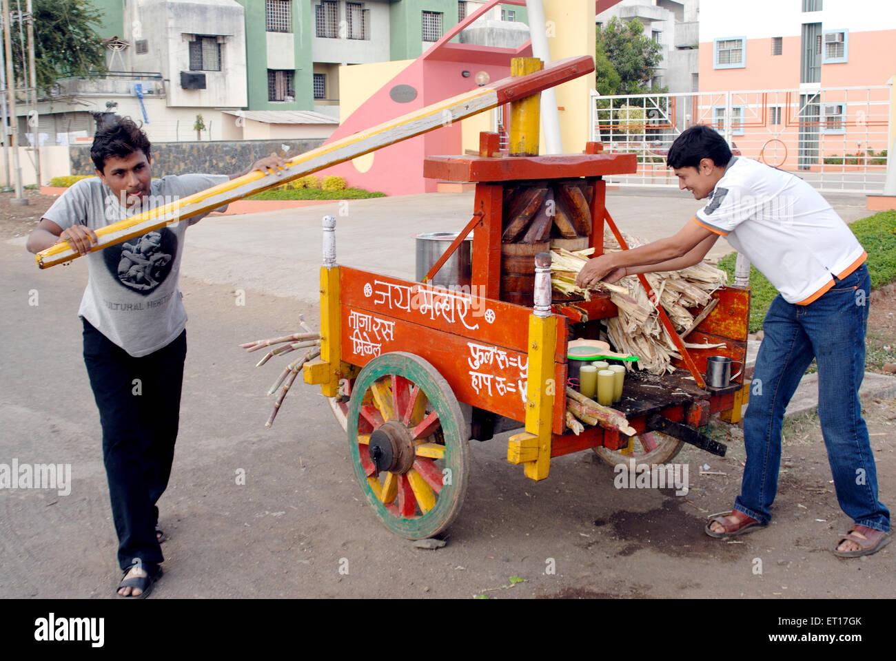 Indian man vendor using manual sugarcane juice extractor machine Nasik Maharashtra India MR#364 - Stock Image