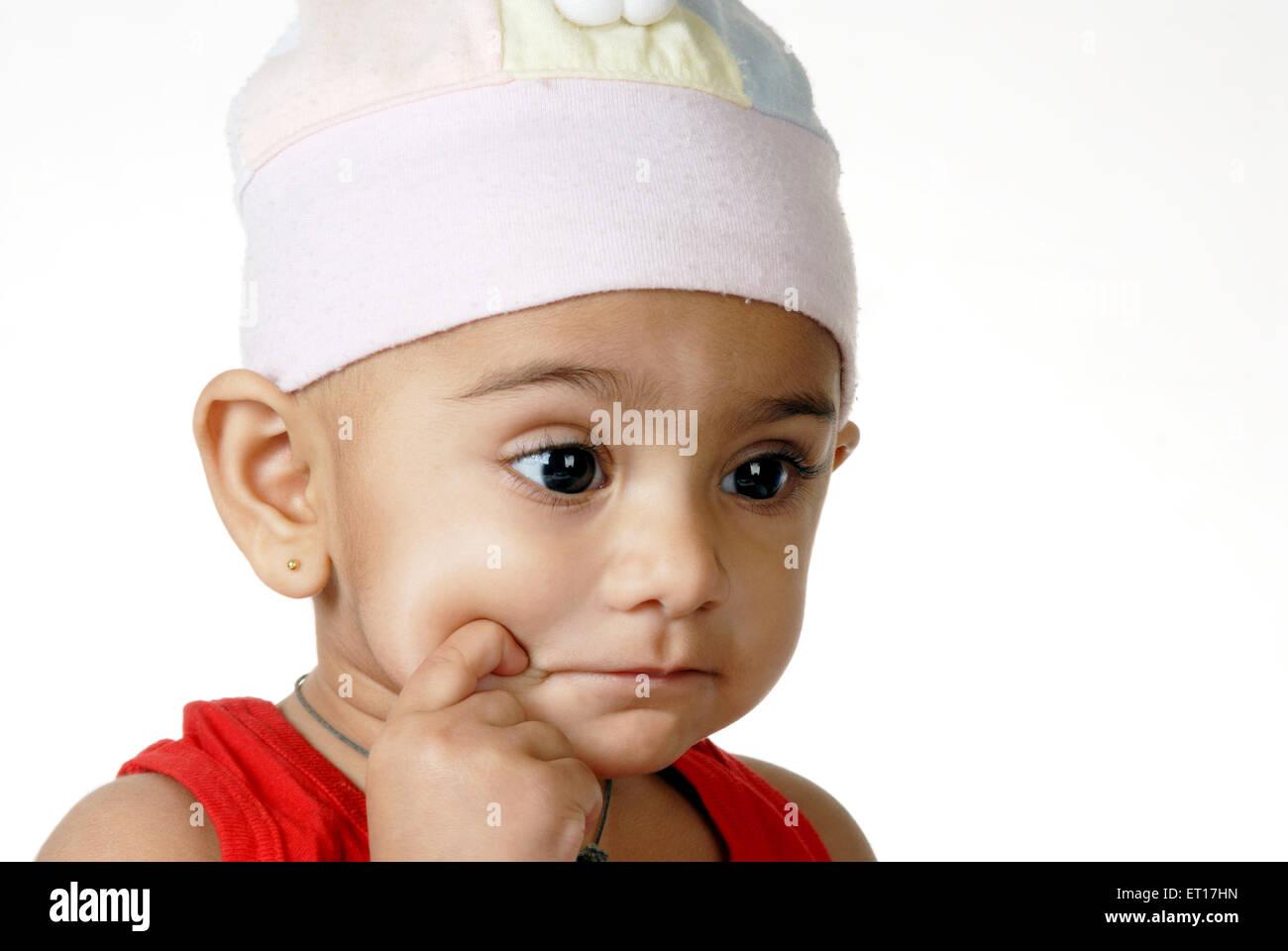 Baby boy thinking , finger on cheeks MR#512 - Stock Image