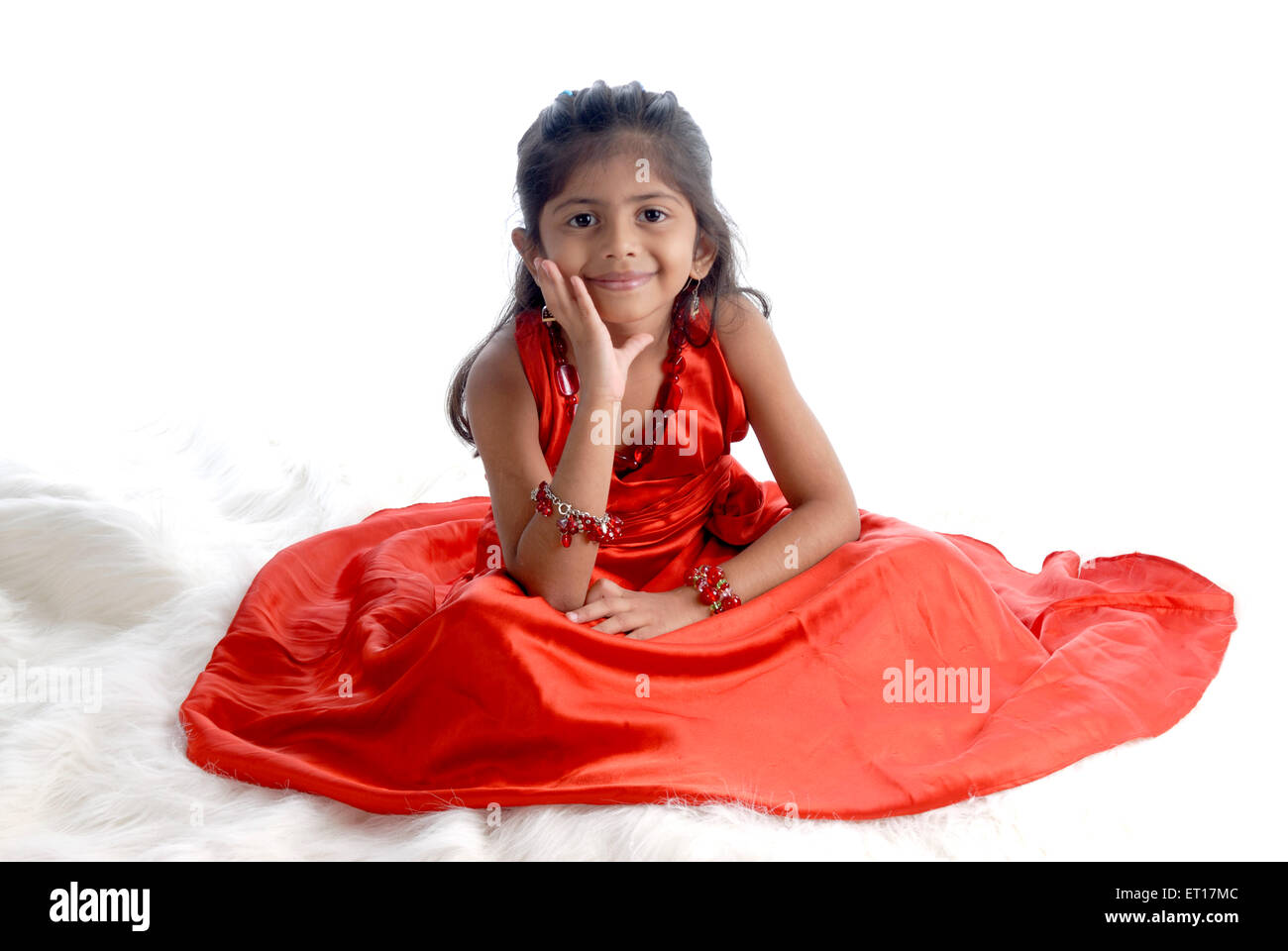 Indian baby girl child sitting hand on face red dress white background - MR#736M - rmm 151197 - Stock Image