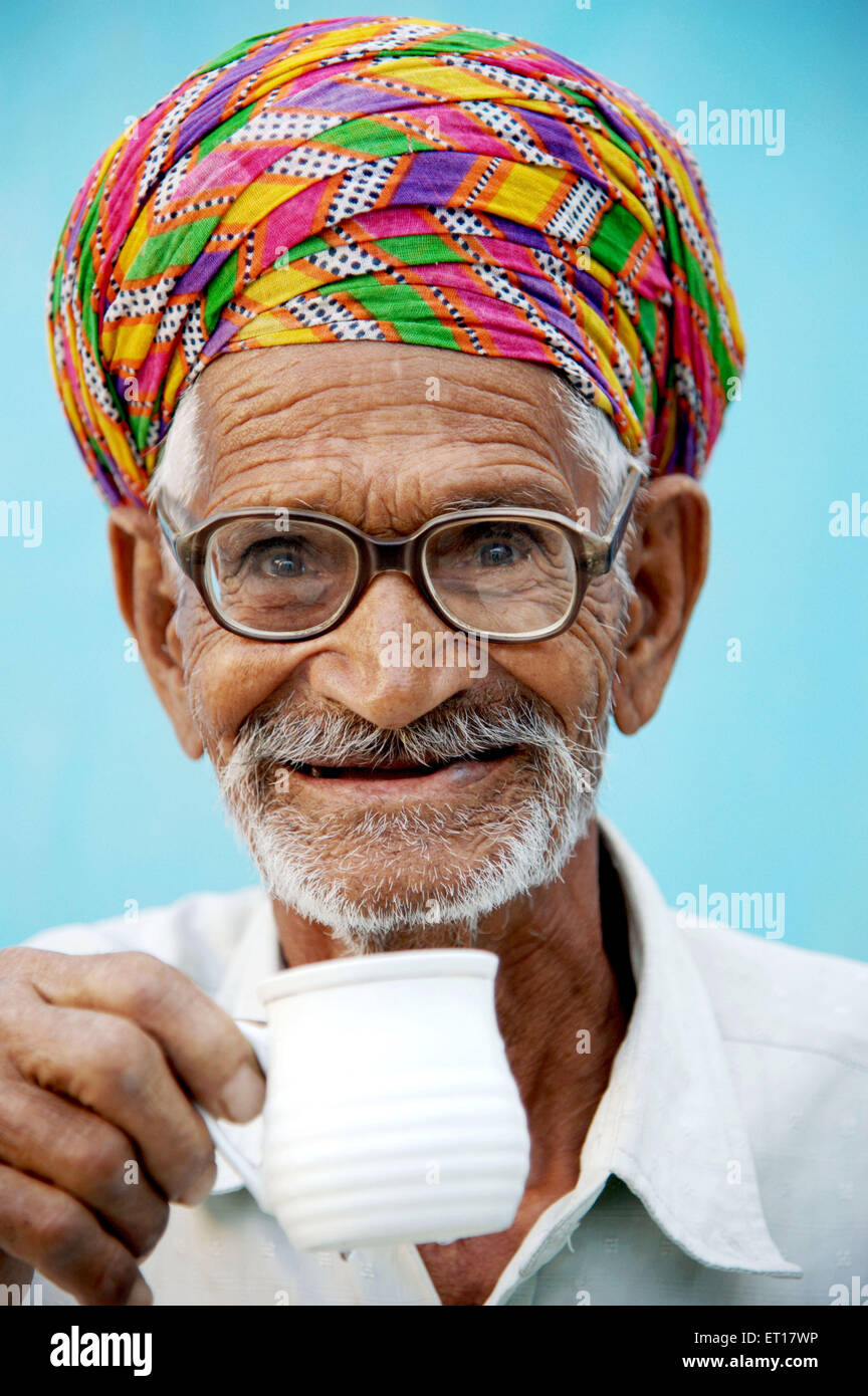 8a5ffdd7d9f83 Old man drinking tea wearing glasses and colorful turban Rajasthan India  Asia MR 784B