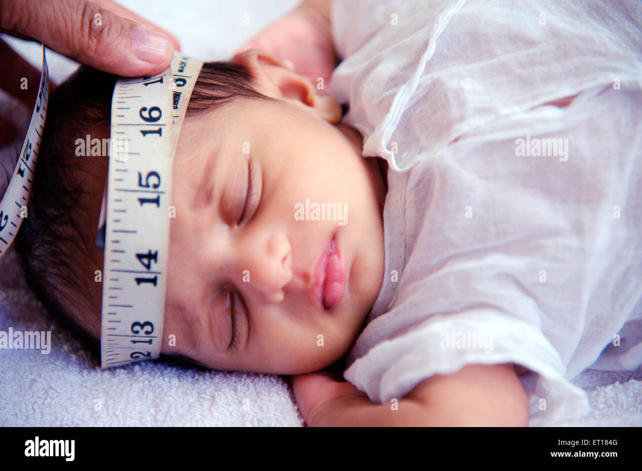 Measuring head of indian new born baby with measure tape - MR#736J - rmm 179686 - Stock Image