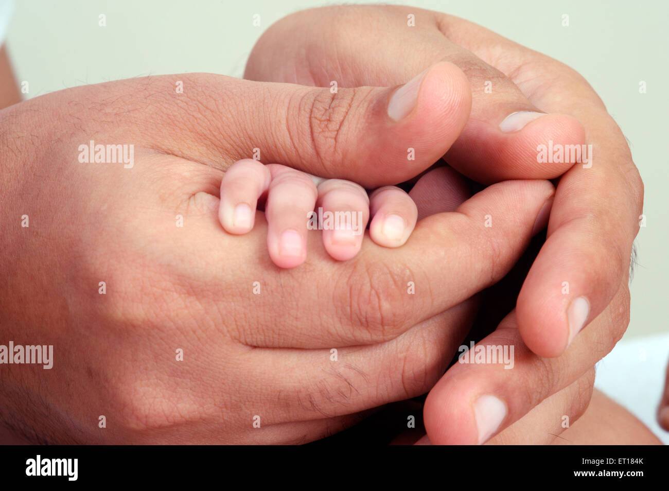 Father holding hand of new born baby - MR#736J and  MR#736LA - Stock Image