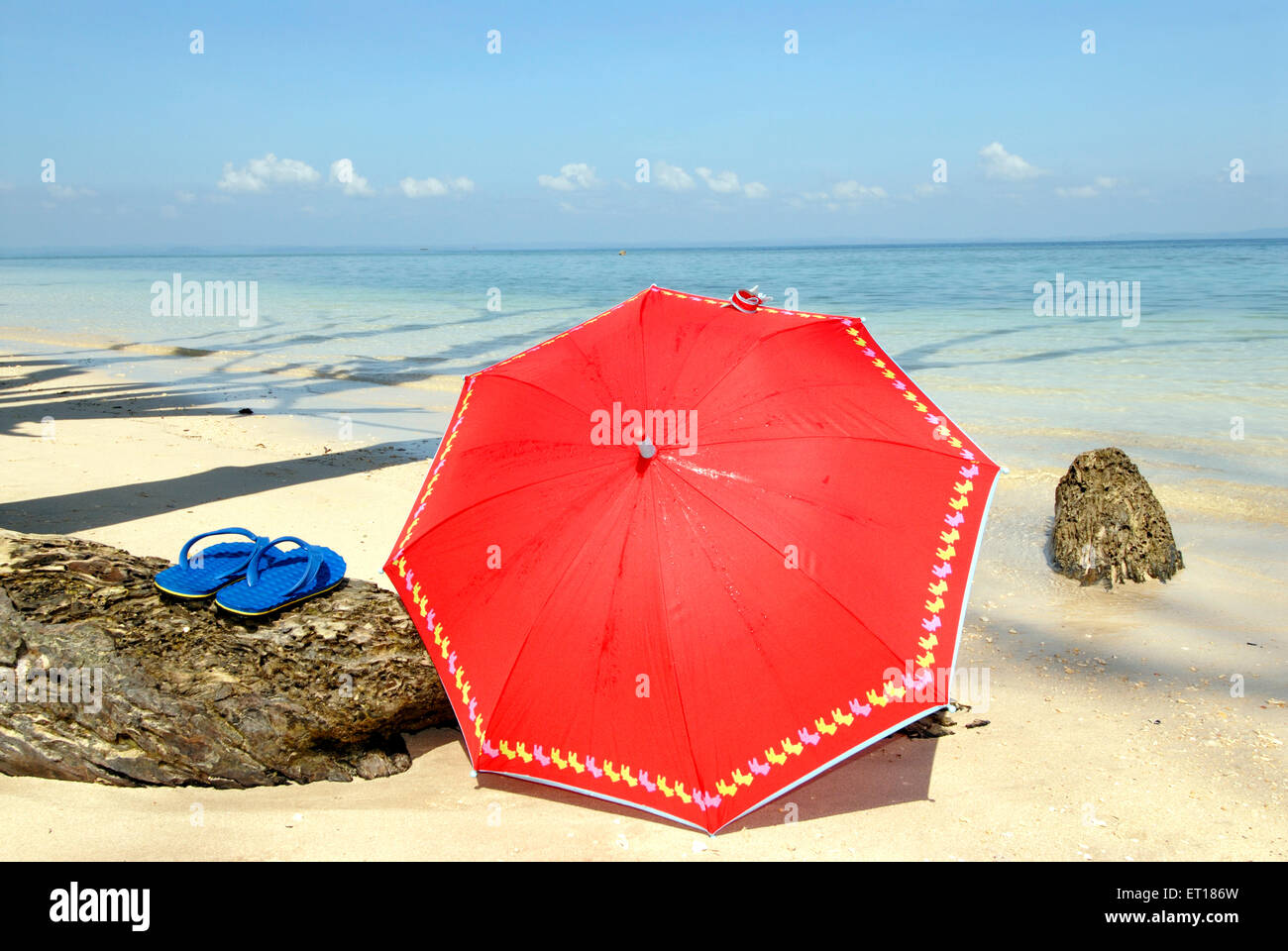 Red umbrella and blue sleeper at Radhanagar beach ; Havelock Islands ; Bay of Bengal Andaman and Nicobar ; India - Stock Image