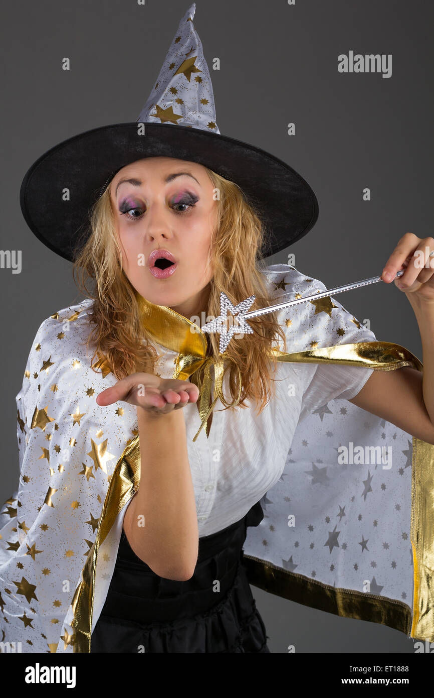 Young witch with magic wand at grey background - Stock Image