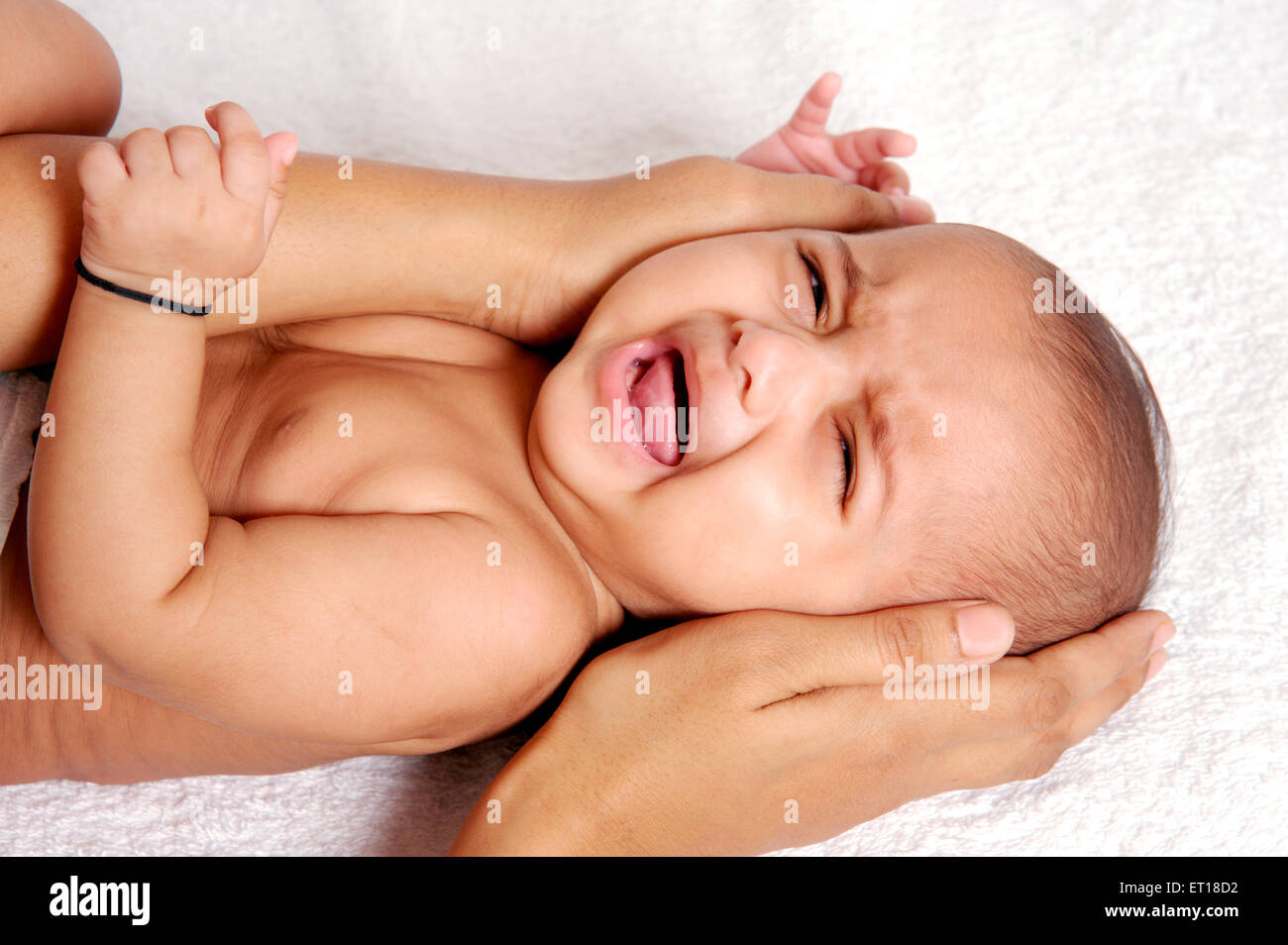 Indian baby Crying Head Protected by Mothers Hand MR#736LA MR#736K - Stock Image