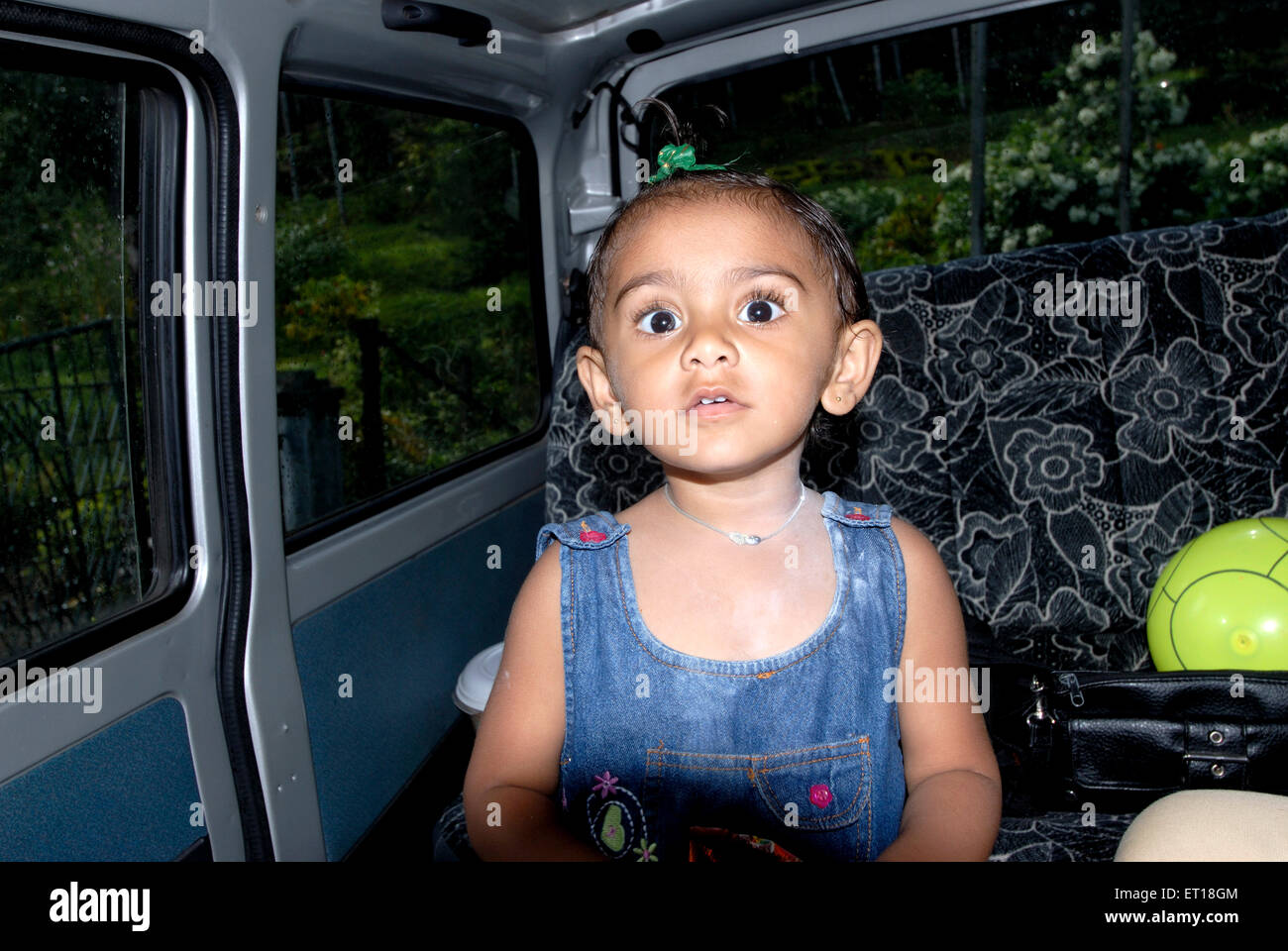 Indian girl child looking surprised eyes wide open sitting in car -  MR#736L - Stock Image