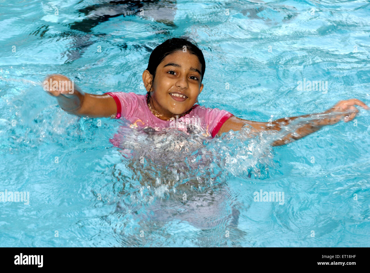 Eight year girl swimming in swimming pool MR# 152 November 2008 - Stock Image