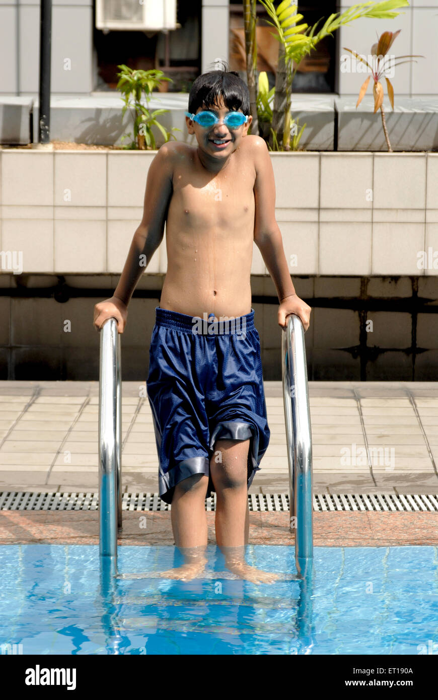 Indian young boy holding railing standing swimming pool India MR#152 -  Stock Image