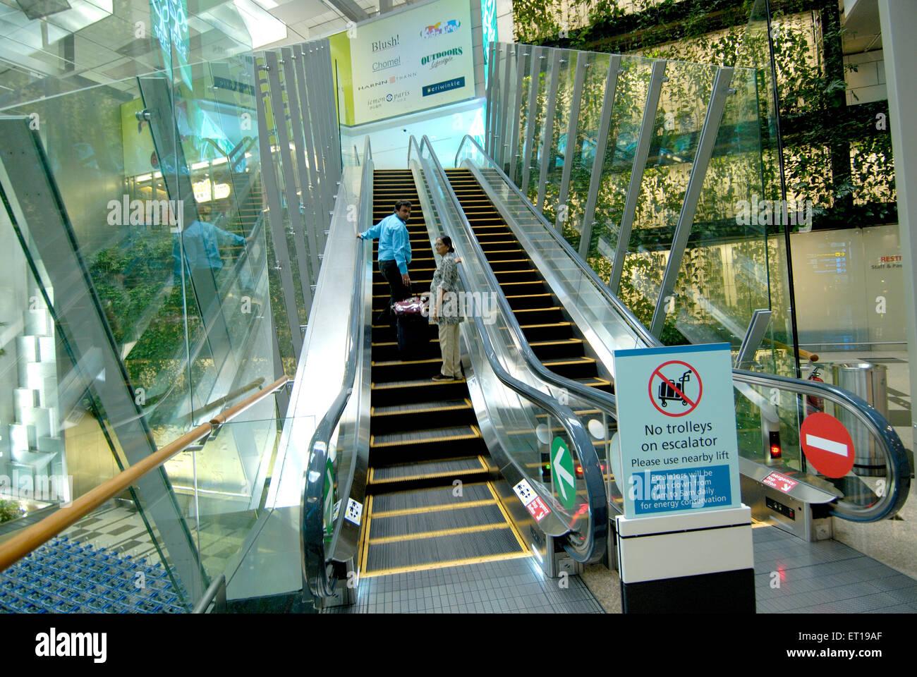 Interior of airport terminal and escalator ; Singapore MR#364 - Stock Image