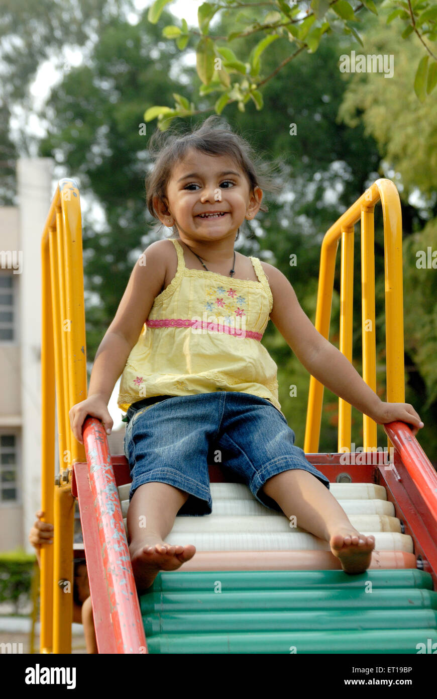 Indian young girl playing on garden slide India MR#736L - Stock Image