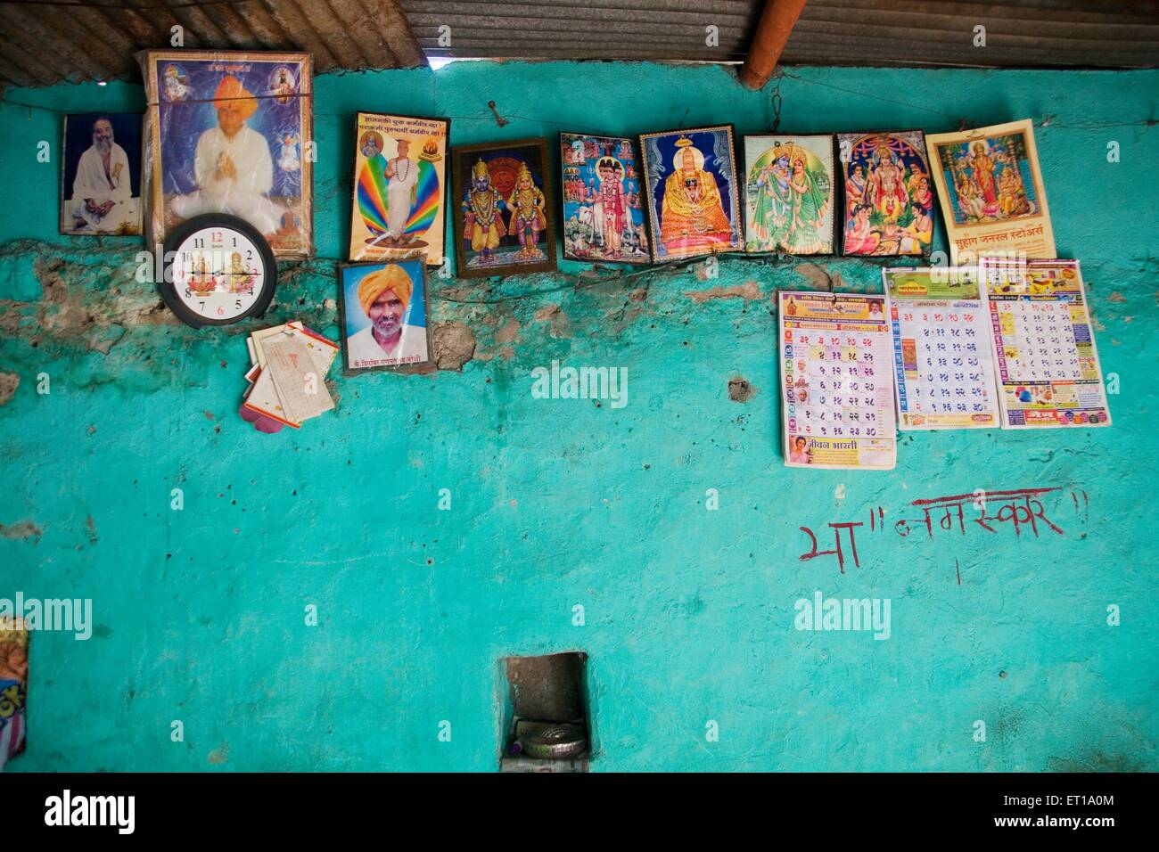 Photographs of gods on wall in house ; Nandur ; Marathwada ; Maharashtra ; India - Stock Image