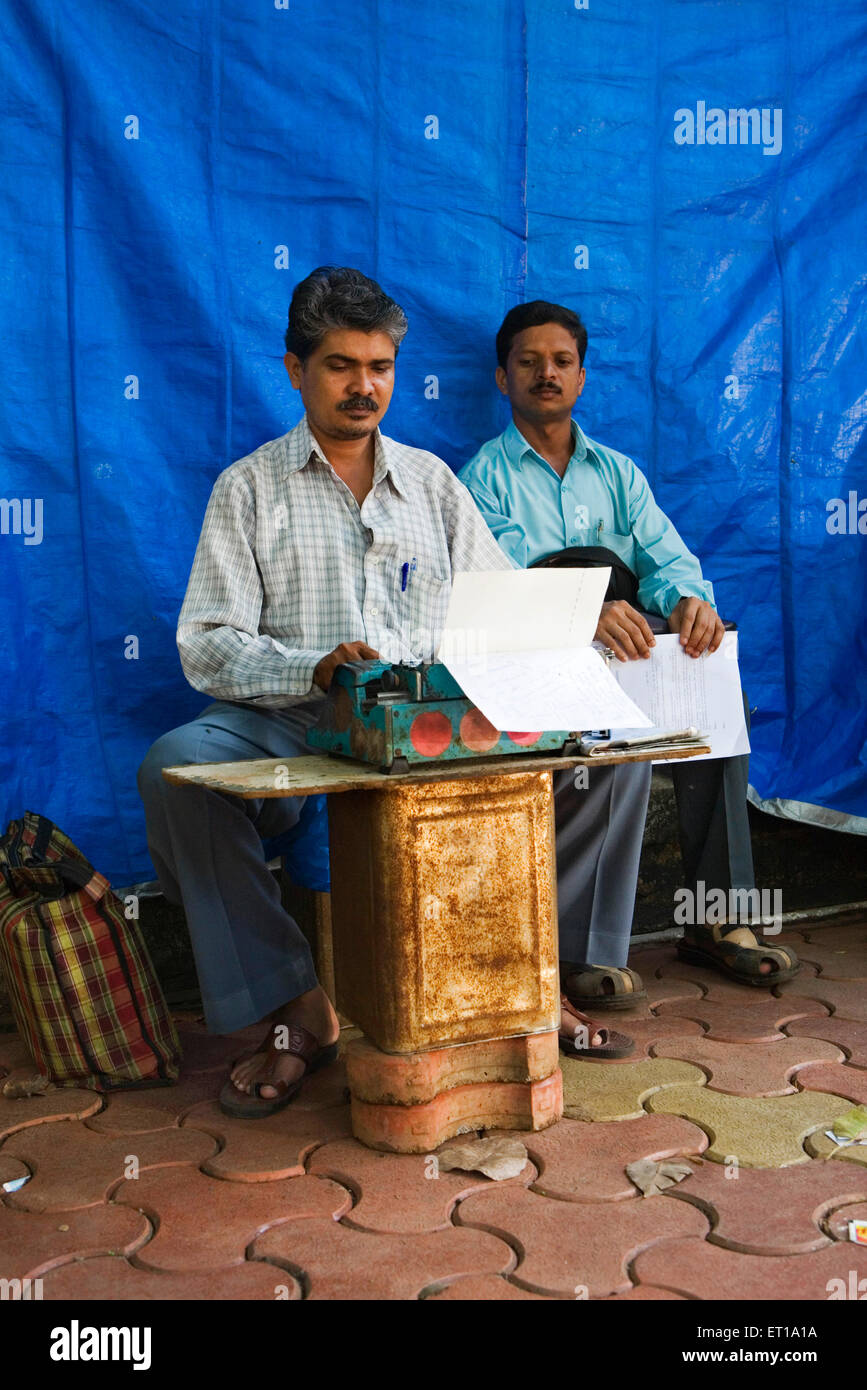 Typist typing legal document on typewriter on footpath outside City Civil Court for client ; Mumbai Bombay - Stock Image