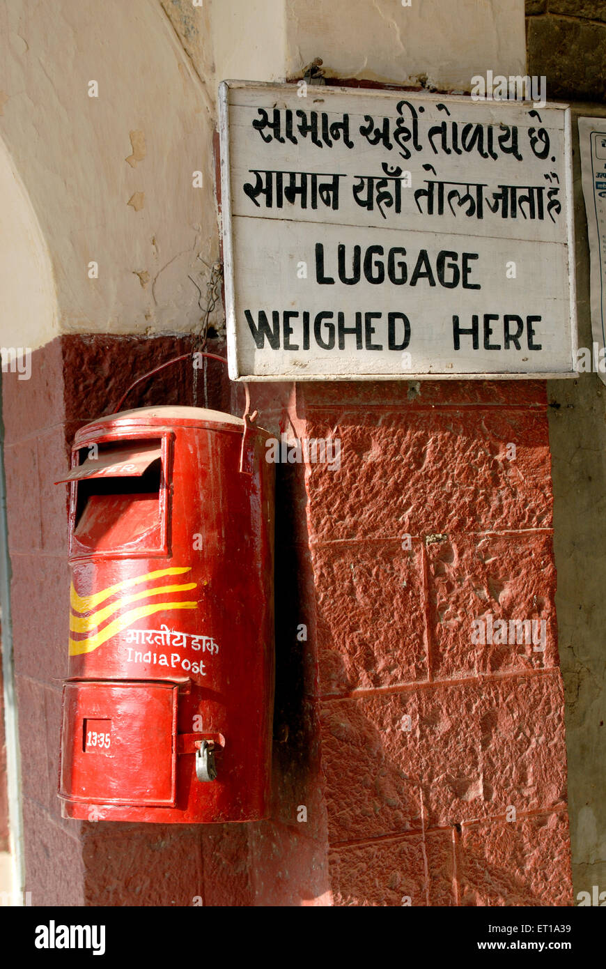 Red postbox at luggage weighed here board - Stock Image