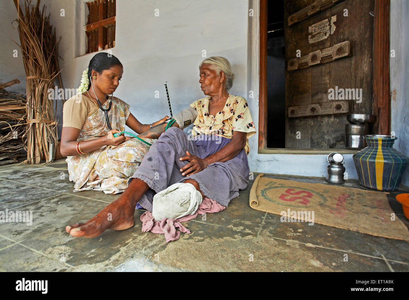 Health worker of NGO Chinmaya Organization of Rural Development CORD checking blood pressure mercury patient doorstep - Stock Image