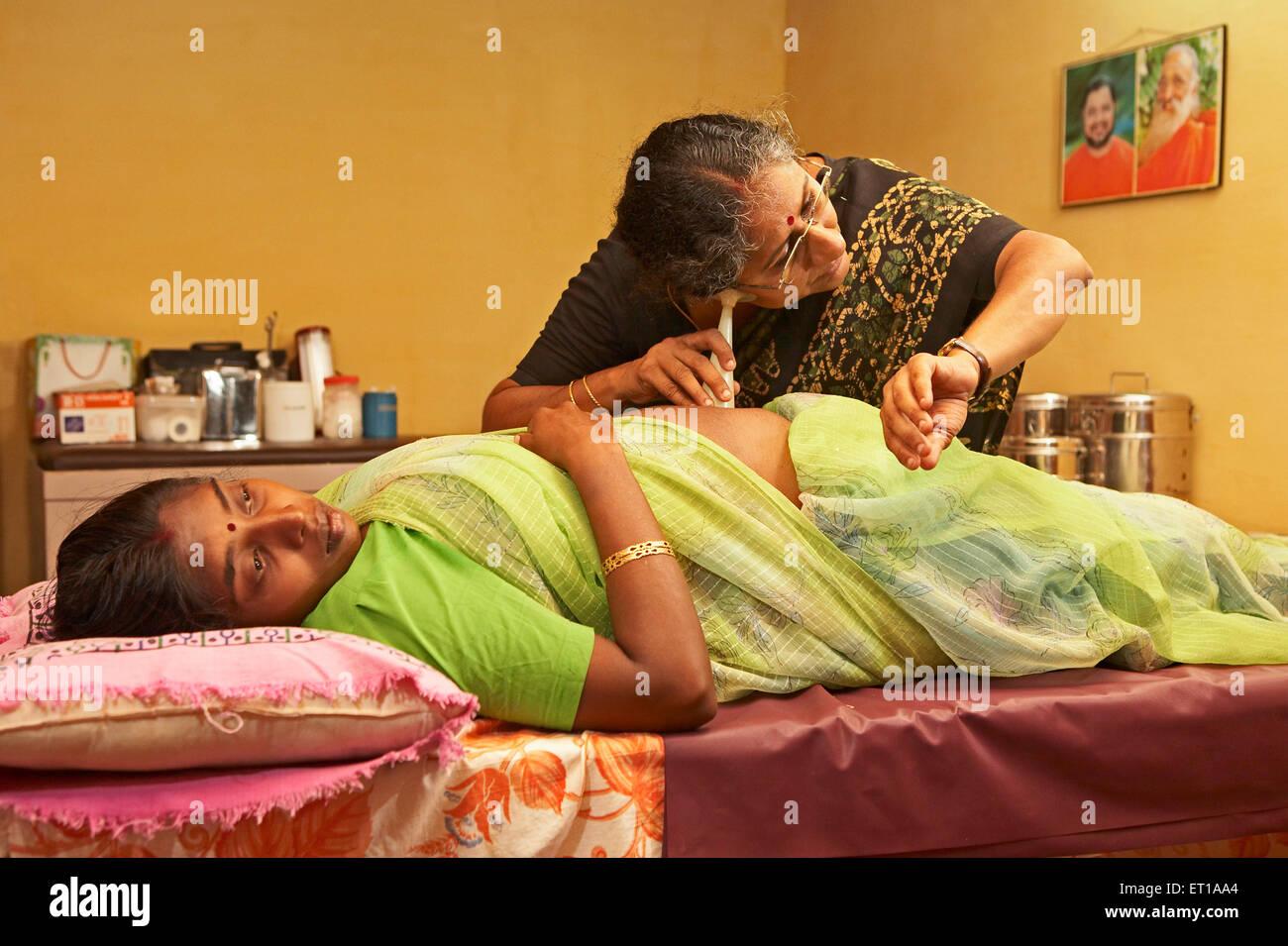 Health worker of NGO Chinmaya Organization of Rural Development CORD using fetal stethoscope on abdomen of pregnant - Stock Image