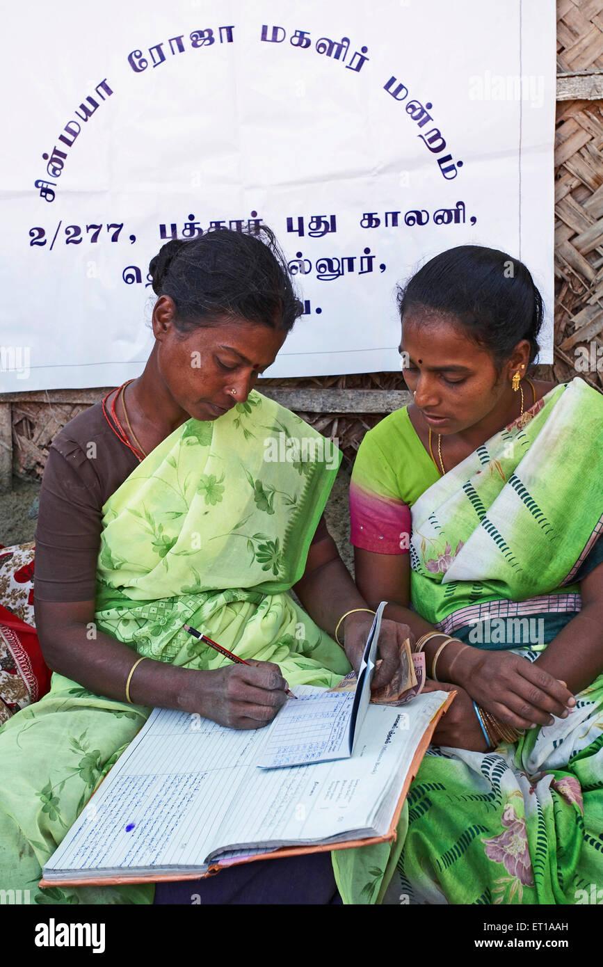 Ladies volunteers of NGO Chinmaya Organization of Rural Development CORD maintaining account book of contribution - Stock Image