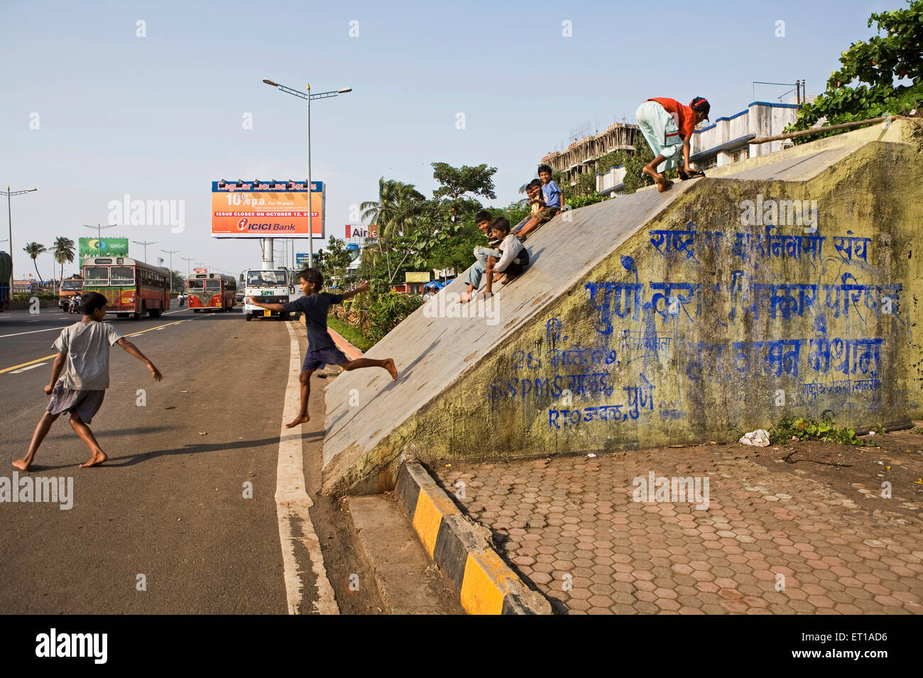 Inclined roof of pedestrian subway along busy western express highway dangerous for children to play game of slide - Stock Image