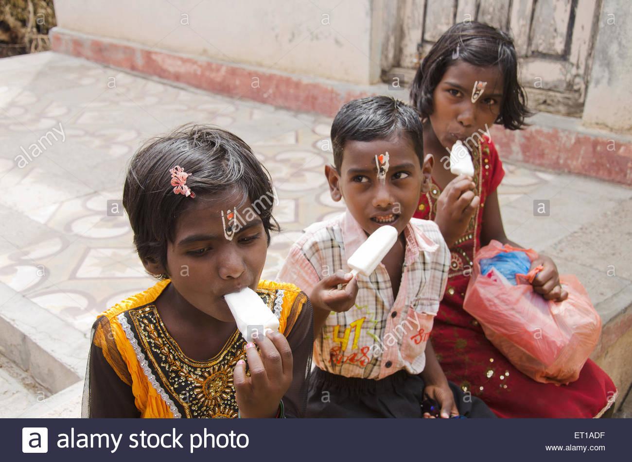 children eating ice creams Pandharpur Maharashtra India Asia MR#RRS005 - Stock Image