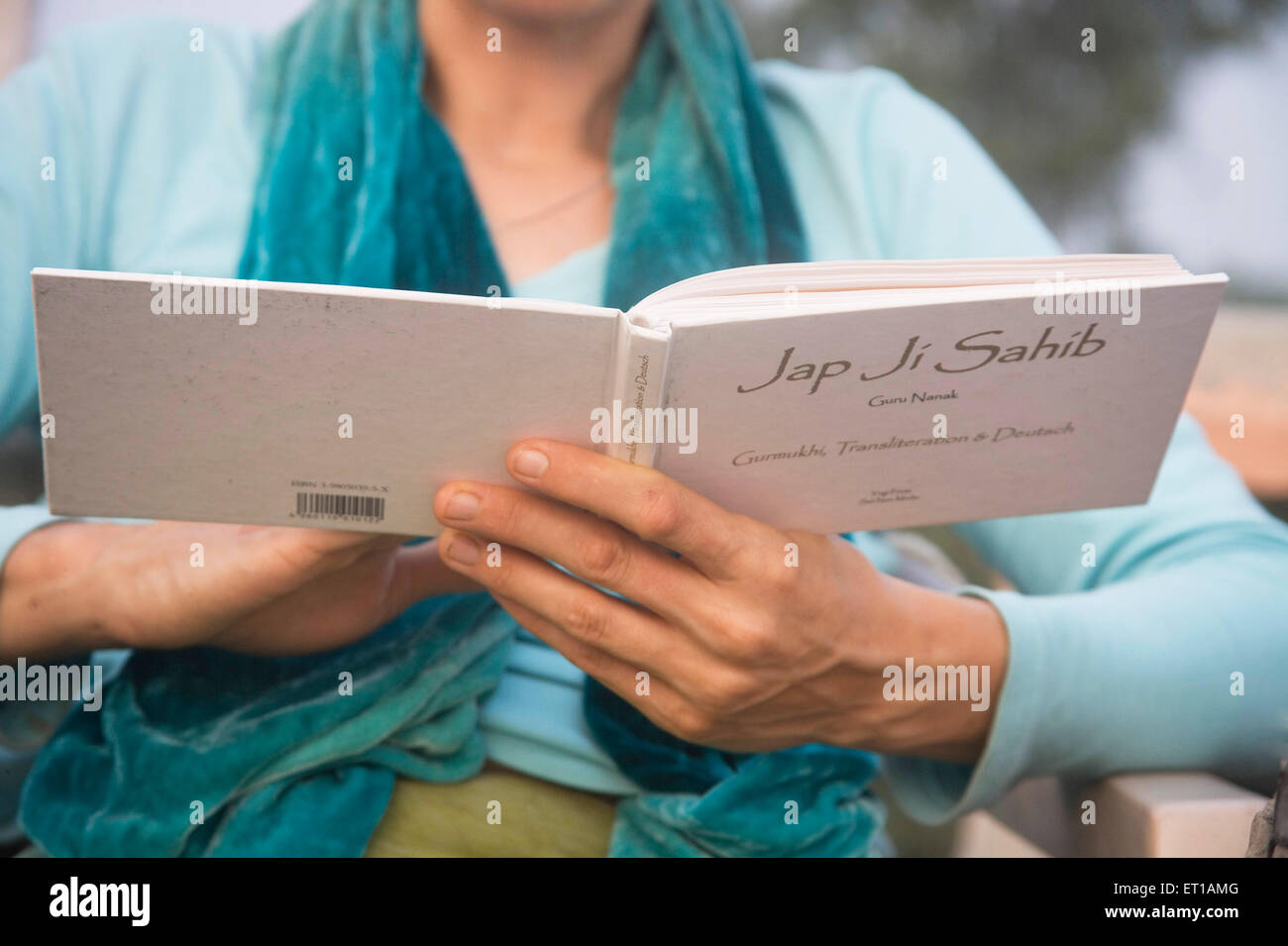 German woman praying holding Jap Ji Sahib Prayer book of the Sikh religion ; Tajgunj ; Agra ; Uttar Pradesh ; India - Stock Image
