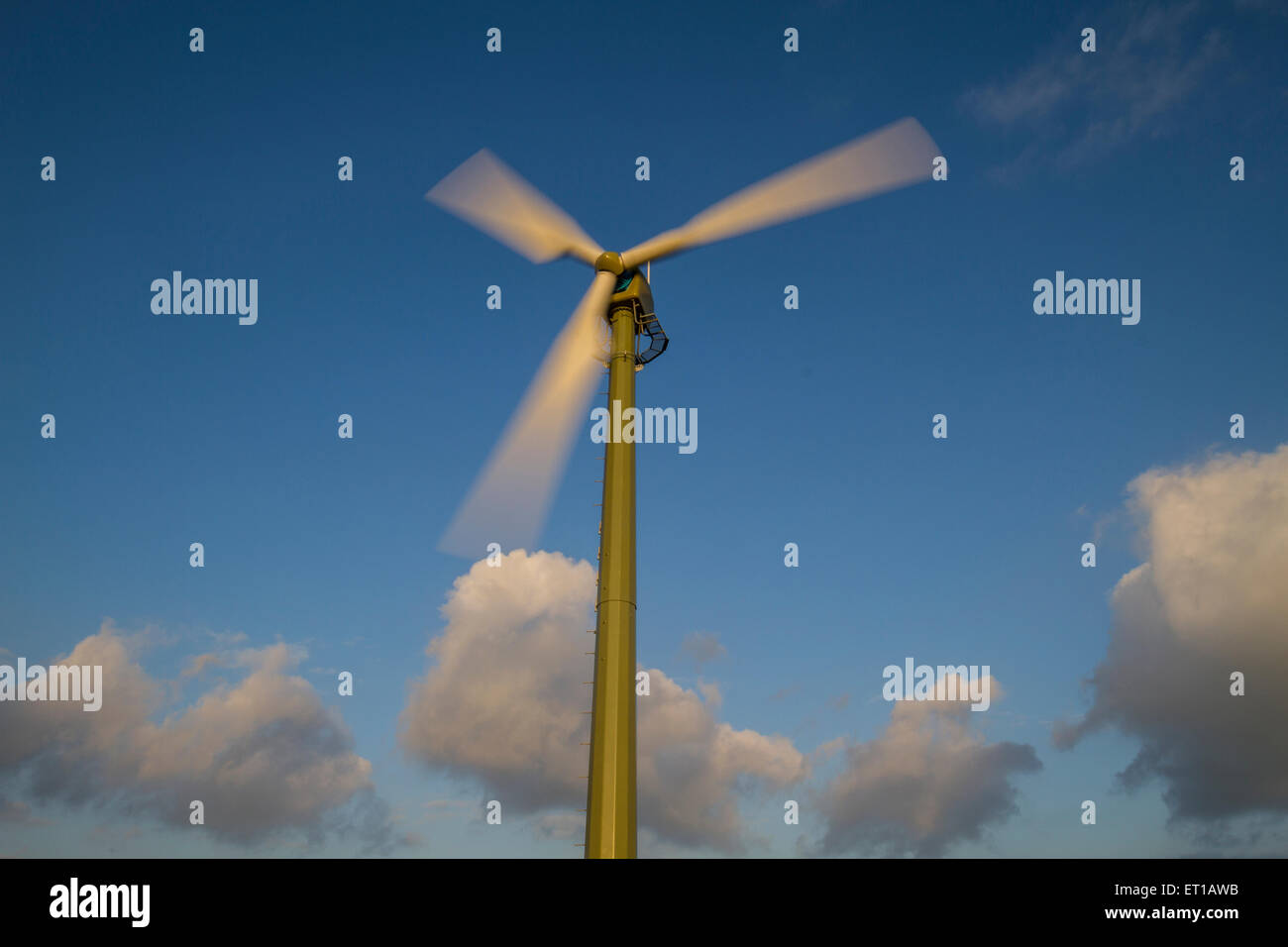 turning wind turbine with vibrant blue sky - Stock Image