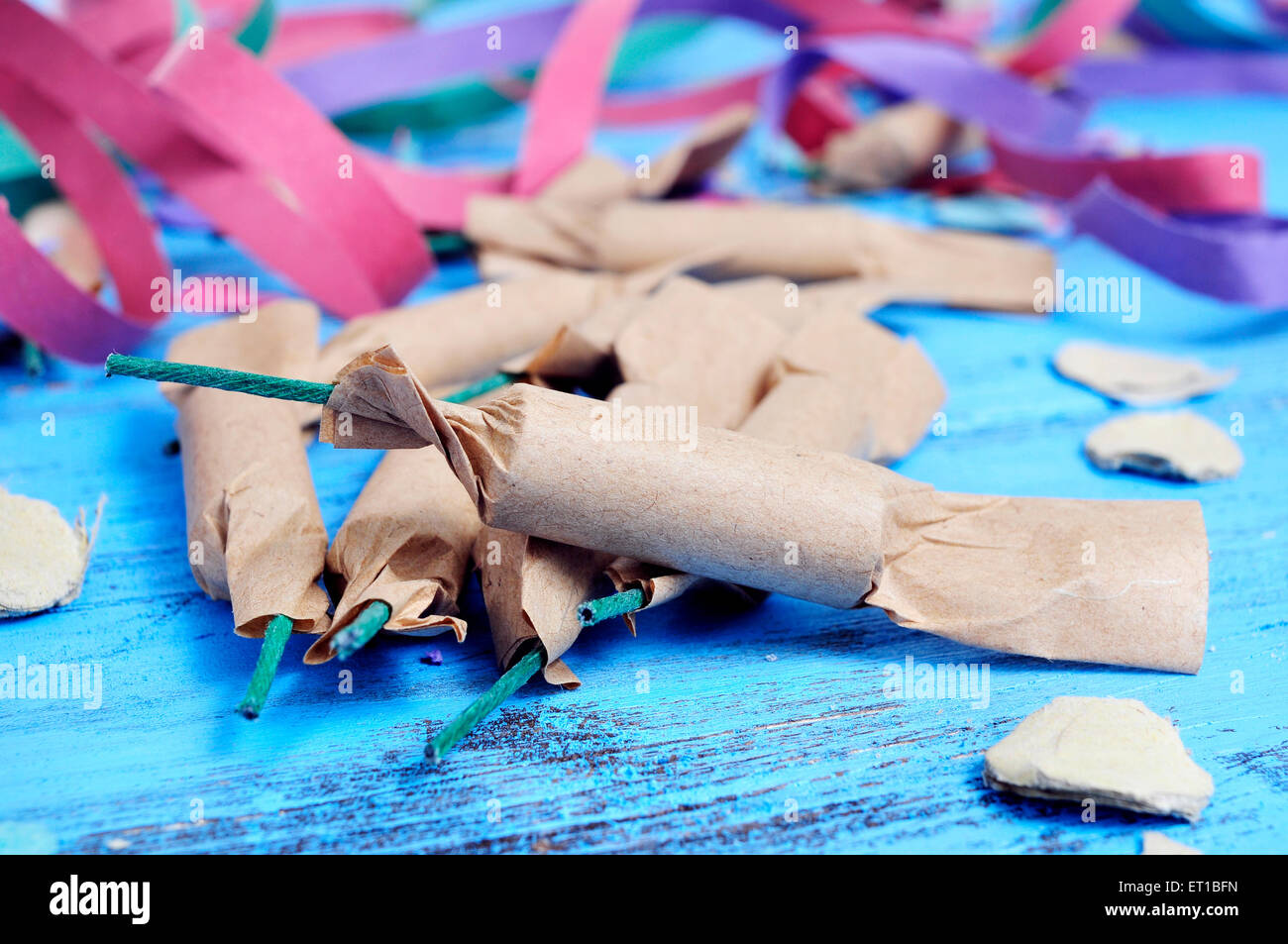 some firecrackers, and confetti and streamers of different colors on a rustic blue wooden surface - Stock Image