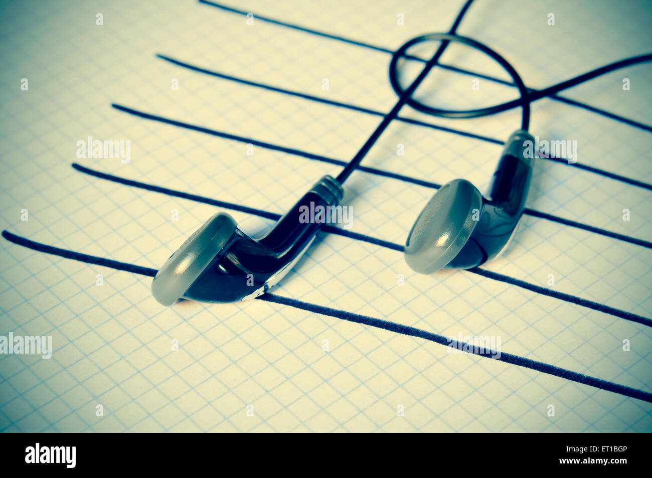 a pair of earphones placed on a staff drawn on a notepad simulating musical notes, with a slight vignette added - Stock Image