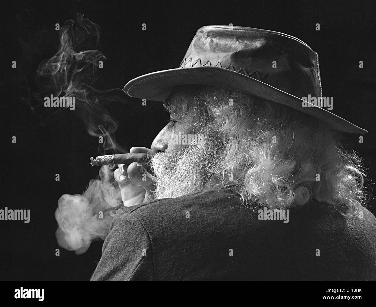 Old man in hat smoking cigar ; Jodhpur ; Rajasthan ; India MR##746B - Stock Image