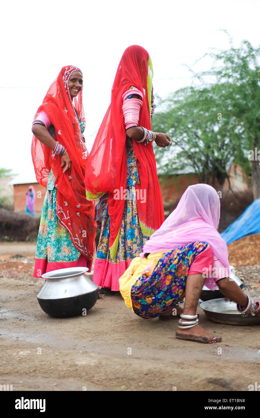 Women washing utensils  ; Rajasthan  ; India NOMR - Stock Image
