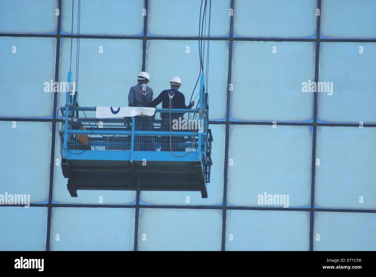 Men cleaning glass of windows ; Delhi ; India - Stock Image