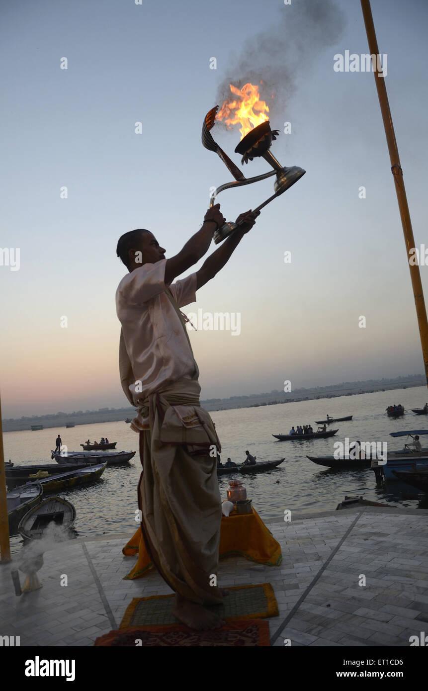 priest is performing ceremonial adoration on Varanasi Ghat Uttar Pradesh India - Stock Image