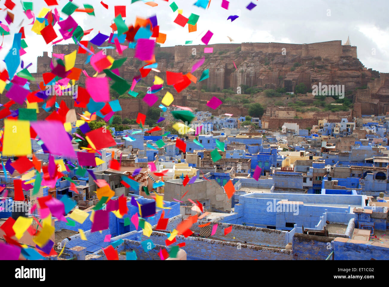 Mehrangarh fort and blue houses colourful pieces of papers flying ; Jodhpur ; Rajasthan ; India Stock Photo