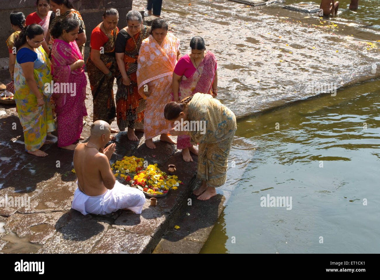 People performing ritual on bank of river NOMR - Stock Image