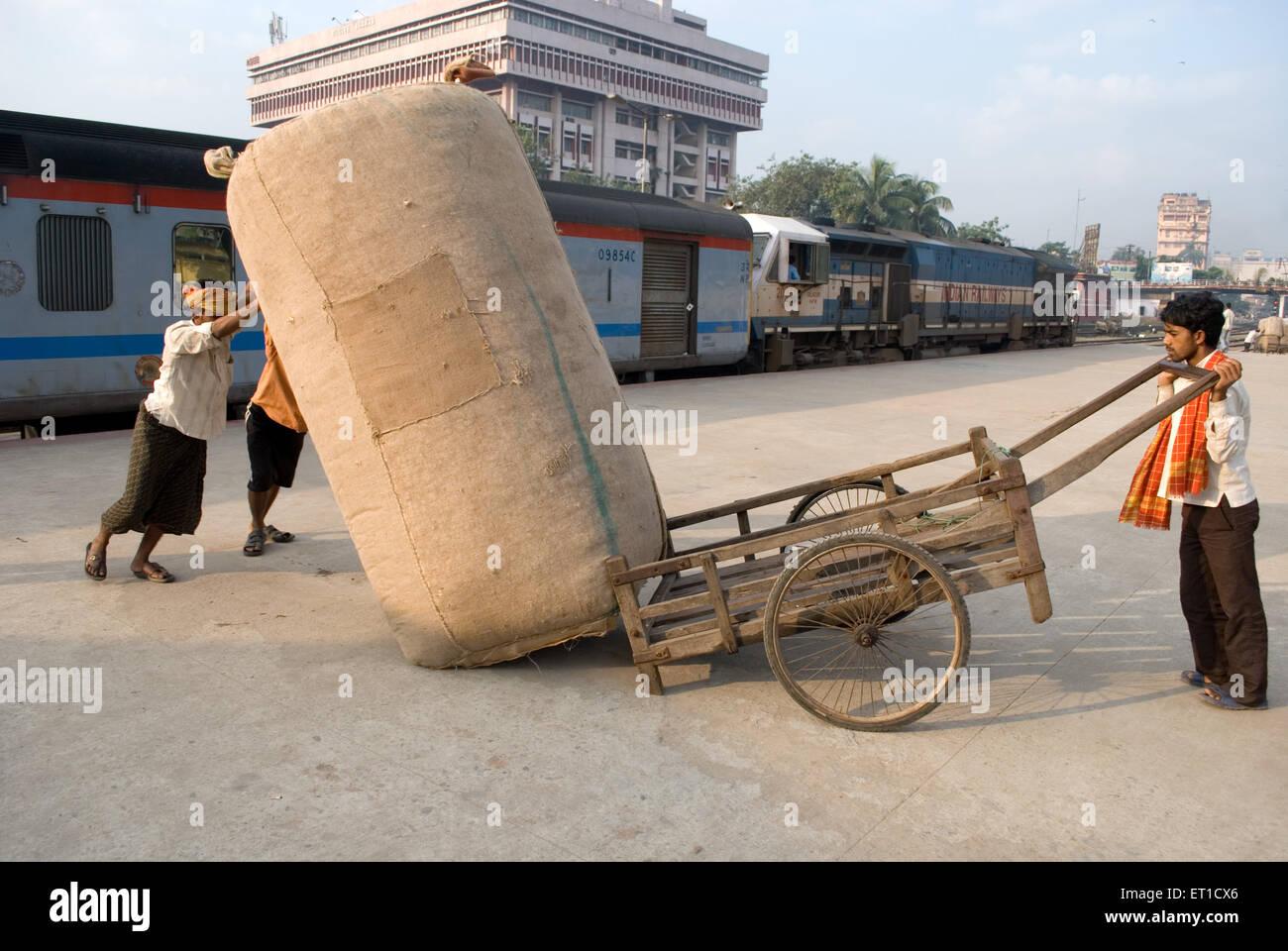 Labourers dragging luggage at railway platform ; Guwhati ; Assam ; India NOMR - Stock Image