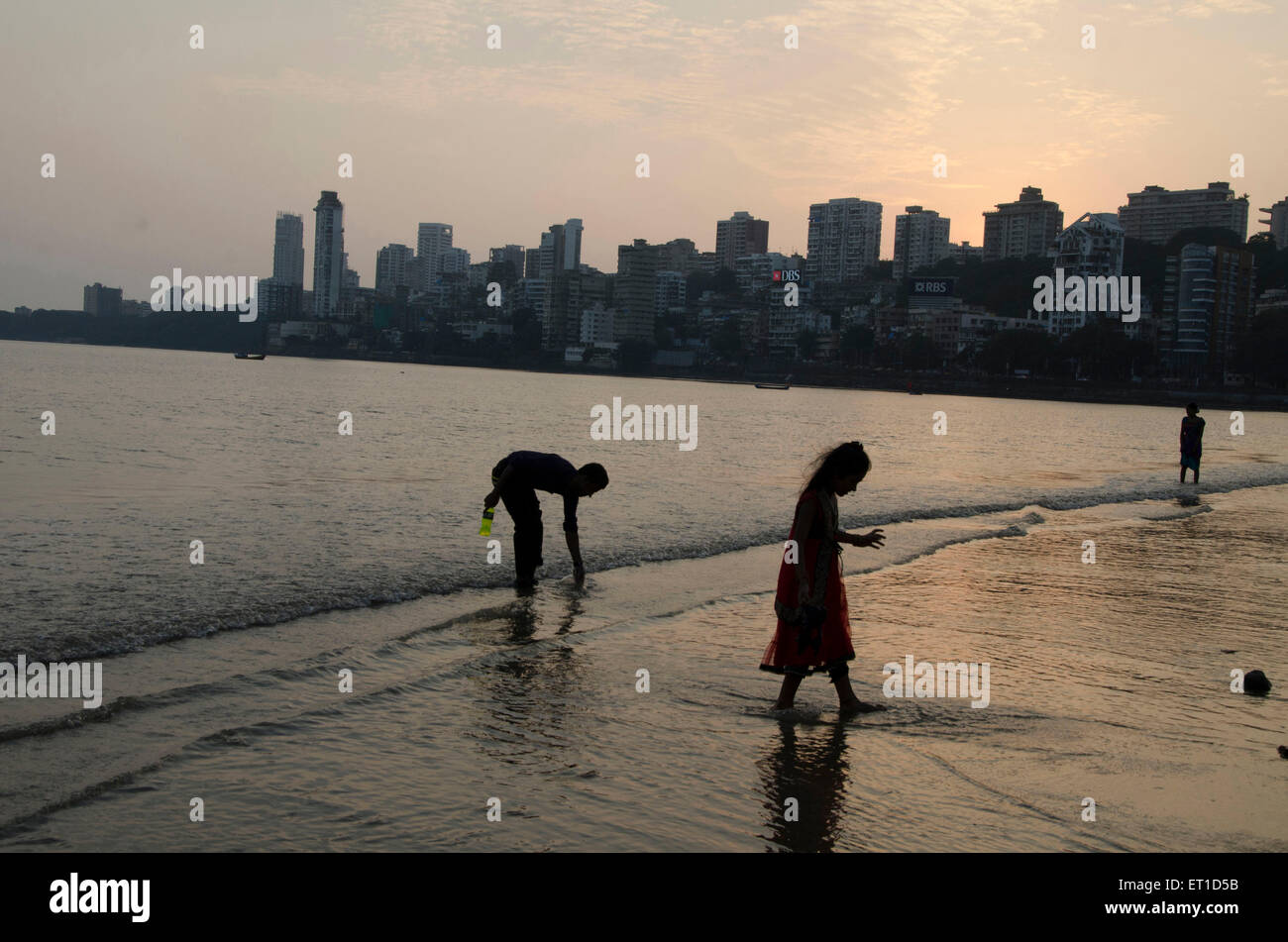 Children Picking Something in sea at Girgaon  Chowpatty Mumbai India Asia - Stock Image