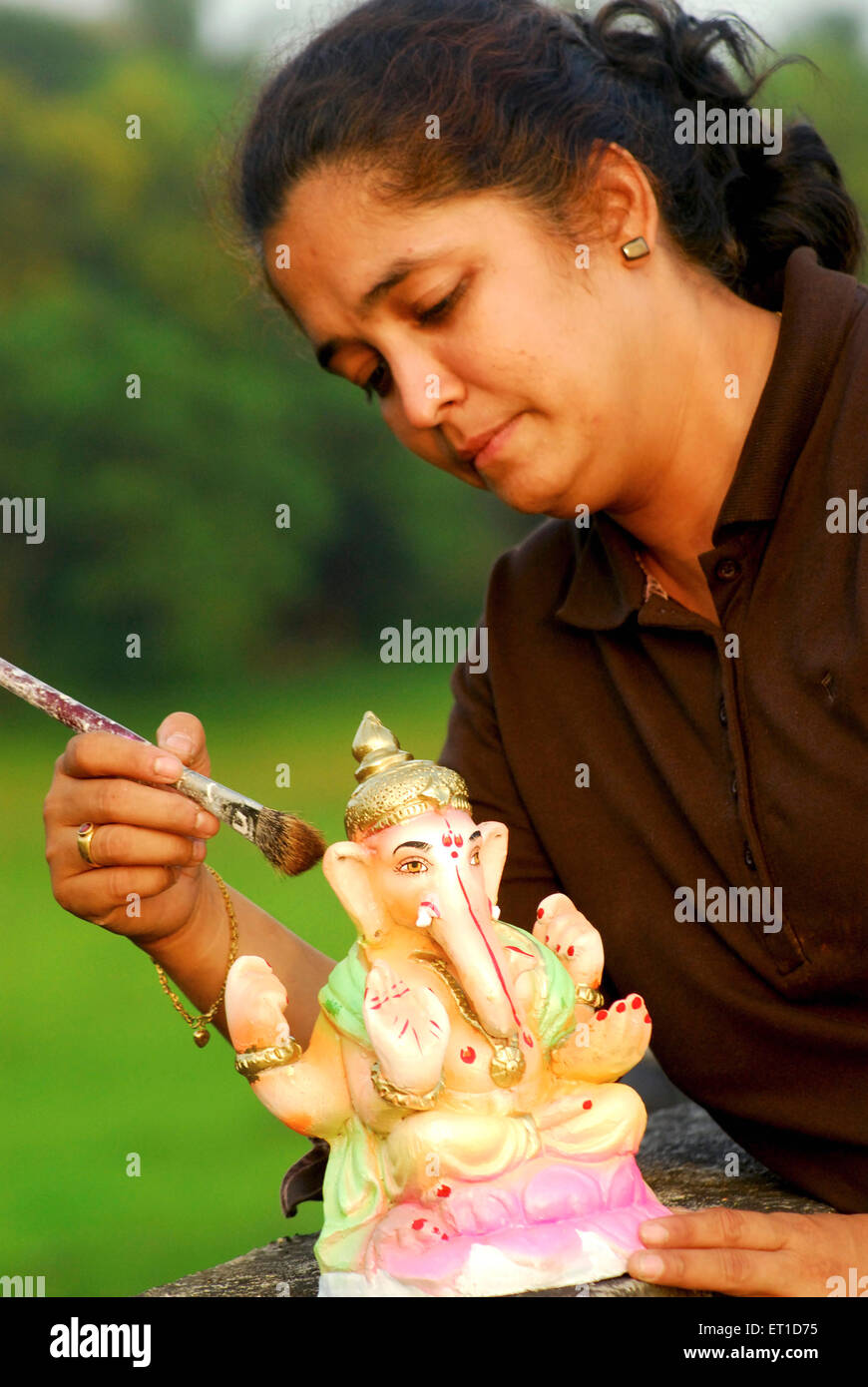 Artist giving final touches to ganesh Idol NO MR - Stock Image