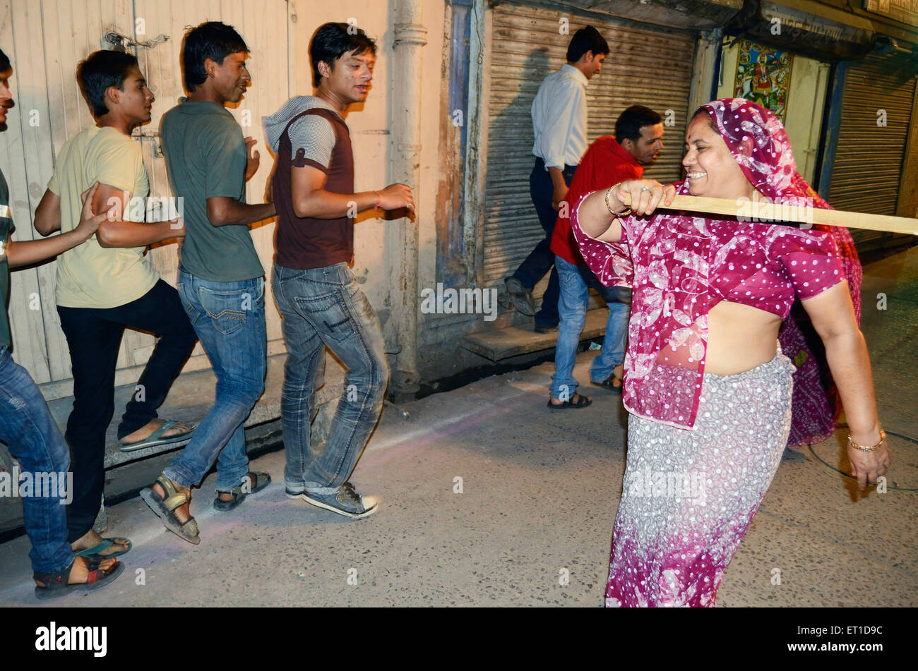 A  woman beating lightly boys with stick  on occasion of Dheenga Gavar festival Jodhpur Rajasthan India NO MR - Stock Image