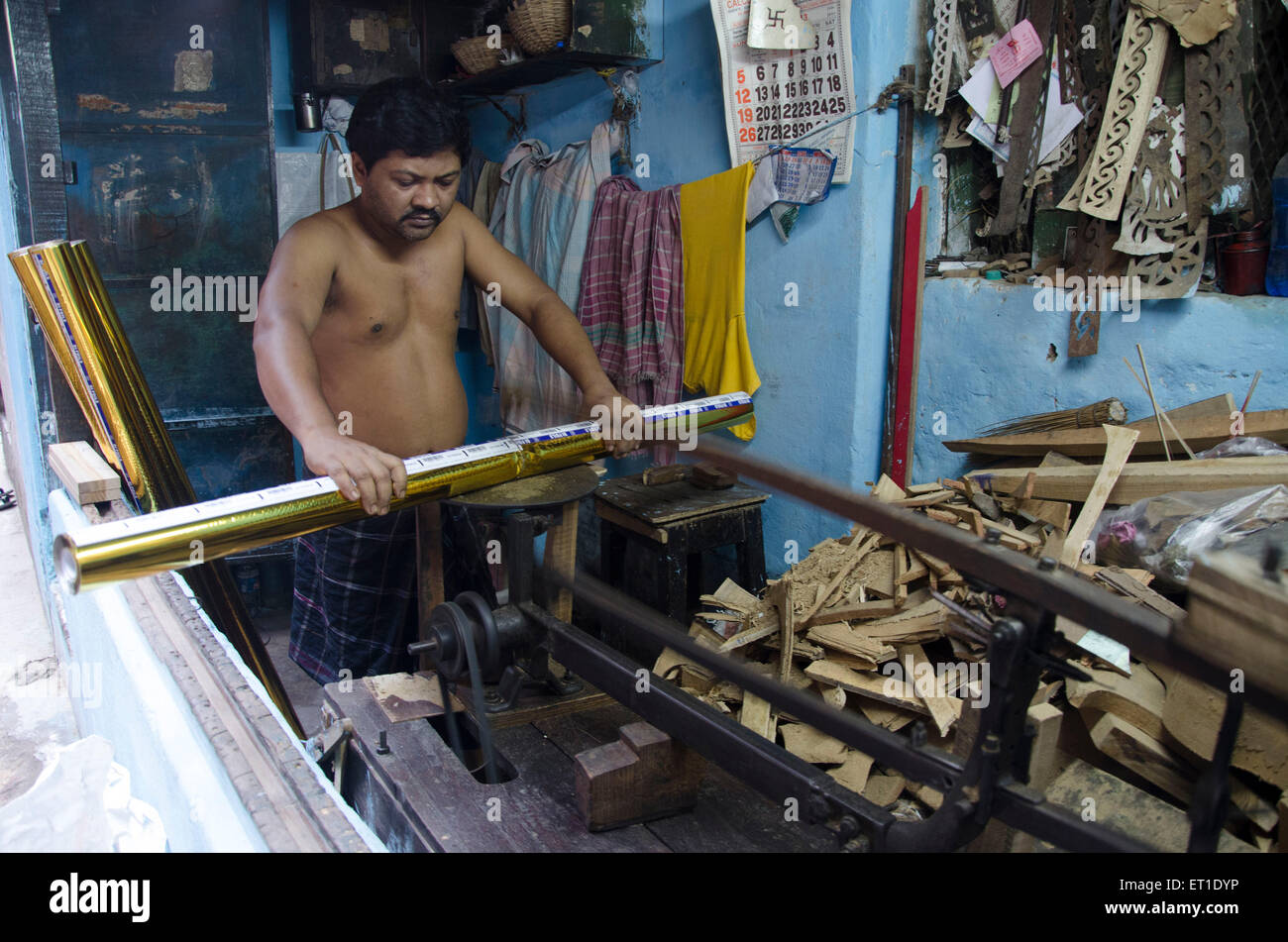 Man cutting decorative coloured paper role  Kolkata West Bengal India Asia - Stock Image