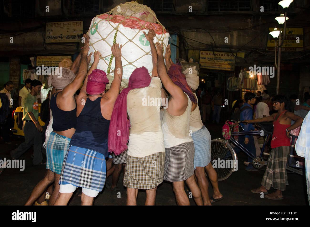 Labourers lifting luggage Kolkata West Bengal India Asia - Stock Image