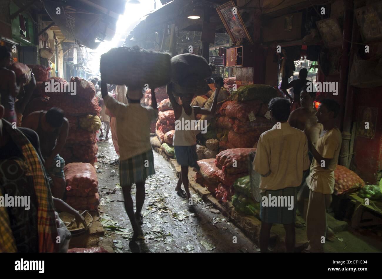 Man carrying vegetables sack in market Kolkata West Bengal India Asia - Stock Image